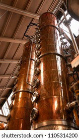 Copper columns stand tall to whiskey still in an American whiskey distillery.