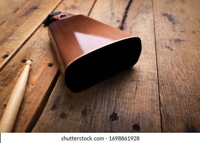 Copper Cowbell musical instrument on a wooden background with drumstick