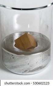 Copper cube floats in a beaker of mercury.