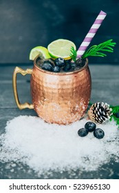 Copper cup with lime and ice on wooden background
