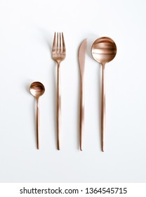 Copper cutlery view from above on a white background. Top view. Knife, tea spoon, fork for a festive table for a wedding, birthday or party.
