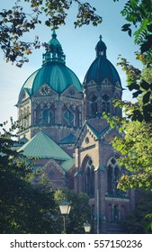 Copper Domes Of St Lukas Church Munich Germany with Clock and Framed By Spring Leaves