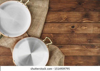 Copper frying pan on wooden background, top view