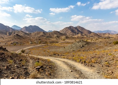 Copper Hike trail, winding gravel dirt road through Wadi Ghargur riverbed and rocky limestone Hajar Mountains in Hatta, United Arab Emirates.