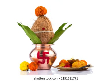 Copper Kalash with coconut and mango leaf and pooja thali with diya, kumkum and sweets with floral decoration on a white background. Essential in hindu puja.