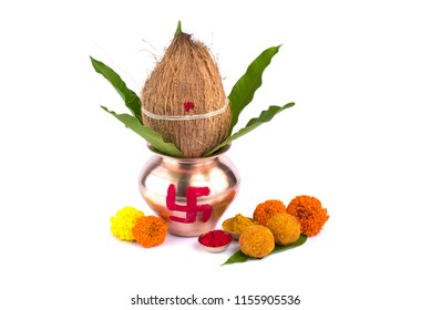 Copper Kalash with coconut, mango leaf, Haldi, kumkum and sweets with marigold flower decoration on a white background. Essential in Hindu puja.