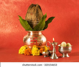 copper kalash with coconut and mango leaf with floral decoration, diya, haldi kumkum and sweet pedha,essential in hindu puja, front view, closeup on red background