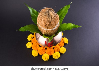 copper kalash with coconut and mango leaf with floral decoration. essential in hindu puja, selective focus, over black background
