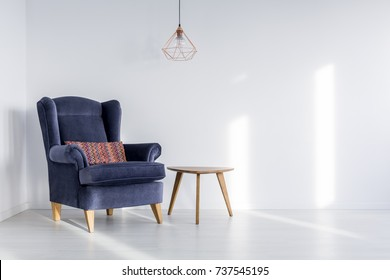 Copper lampshade hanging above dark blue armchair with colorful pillow in room with white empty wall