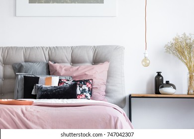Copper light bulb and glass vases on wooden table next to big comfy bed with soft gray headboard and pastel bedding