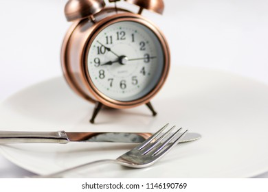 copper look clock with knife and fork in white background