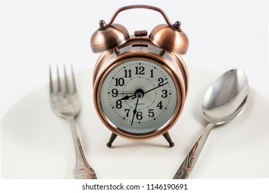 copper look clock with spoon and fork in white background