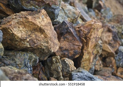 Copper mineralised rock pile, rubble tailings, close with shallow depth of field.