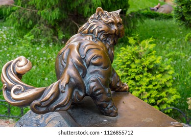 A copper monument to a large, pushy cat looking back