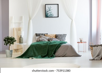 Copper nightstand and ladder blanket rack next to big bed with green quilt in white bedroom of spacious apartment