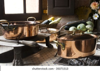 Copper pans on 17th century coal stove in preserved kitchen in an old chateau in Burgundy, France. Still life with fruit and natural light.