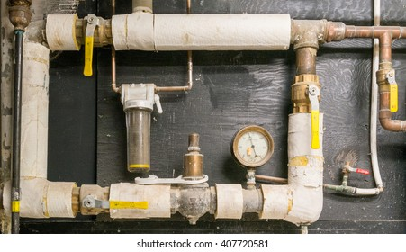 Copper pipes with valves and thermal isolation mounted on the wall