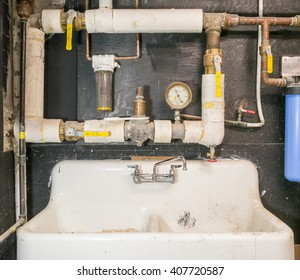Copper pipes with valves and thermal isolation mounted on the wall above the sink