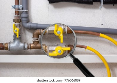 Copper and plastic pipes and yellow valves in a boiler room under the magnifying glass