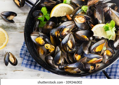 Copper pot of gourmet mussels served on a napkin garnished with lemon slices. Top view