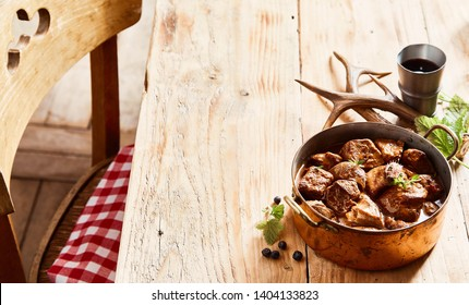 Copper pot of rich tasty deer venison goulash seasoned with herbs served on a rustic wood table with fresh seasoning, beaker of red wine and antlers