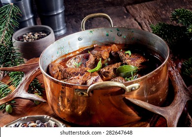 Copper Pot of Venison Goulash Stew Seasoned with Fresh Herbs Surrounded by Evergreen Sprigs and Deer Antlers