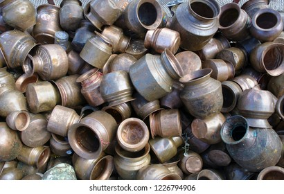 Copper pots are collected in a pile to collect and pour water on Lord Shiba Lingam