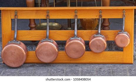 Copper pots cookware set at wooden shelf