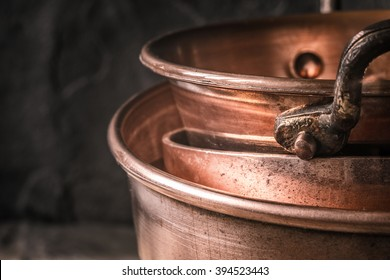 Copper pots and pans on the blurred background