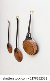 Copper pots and utinsils hanging on a white painted wall on a kitchen. Rustic handmade style kitchen concept