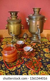 Copper samovars honey and tea cups with Khokhloma painting Copper samovars, honey and tea cups with Khokhloma painting on the table. Jurmala. Latvia. April 1, 2019