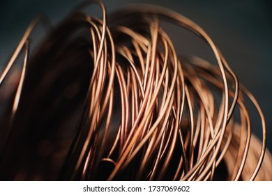 Copper scrap metal, wire, windings of motors and transformers, electrical wire without insulation. Against the background of a copper sheet. Close-up. Macro.