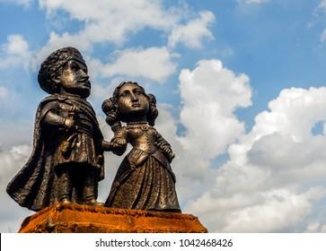 Copper sculpture of the medieval couple against a blue sky with clouds in Palanok Castle, Mukacheve, Western Ukraine