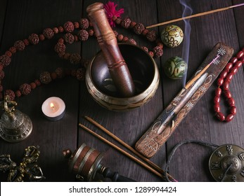 Copper singing bowl, prayer beads, prayer drum, stone balls and other Tibetan religious objects for meditation and alternative medicine on a wooden background