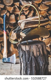 Copper stack of wood firewood is stacked on a tree stump in front of logs. Nearby stands an ax with a long handle