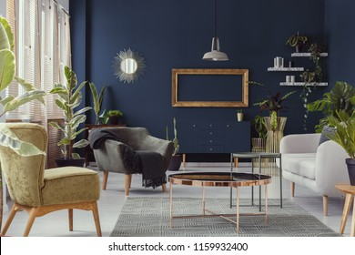 Copper table between armchairs and sofa in blue living room interior with mockup and mirror. Real photo