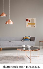 Copper table and lamps in a grey living room interior. Real photo