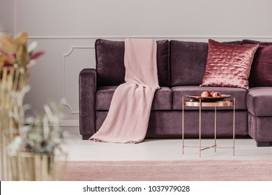 Copper table near violet sofa with pink blanket and cushion in woman's living room interior