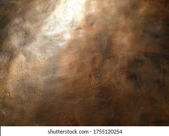 Copper texture background. Bronze texture. Bent metal with dents. Close-up of a bronze surface. A reflection of light in a bent place