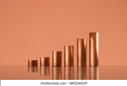 Copper tubes forming a growing bar graph, copy space. Trading and commodity supercycle concept, copy space.
