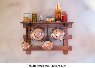 Copper utensils hanging on the shelf: colander, dipper, frying pan, jars, cutting board