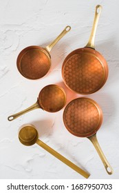 Copper utensils on the white background. Vintage copper cookware - cocottes, creamer and accessories for coffee.