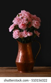 A copper vase with pink miniature carnations in dramatic lighting with a black background on a textured wood table.