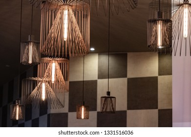Copper wire chandeliers with chess check wall backdrop. Modern metal lampshades. Lamp with long light bulb. Abstract background. Geometric lines and shapes. Futuristic interior decoration