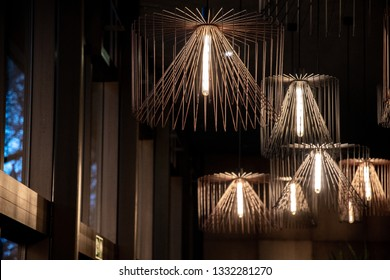 Copper wire chandeliers in interior near windows. Urban style metal lampshades. Hanging lamps with long light bulbs. Abstract background. Geometric shapes of different sizes. Interior decorations