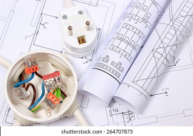 Copper wire connections in electrical box, electric plug and rolls of electrical diagrams on construction drawing of house, energy concept