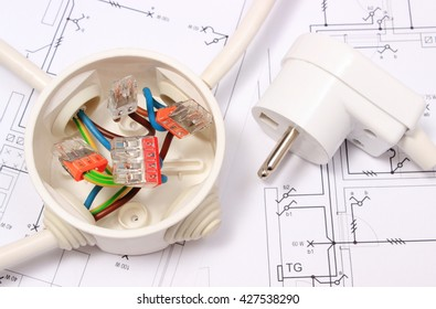 Copper wire connections in electrical box and electric plug lying on construction drawing of house, accessories for engineering work, energy concept