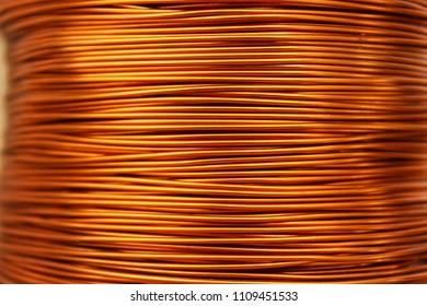Copper wire for electronics close-up with a focus on the center and blurred edges of the right and left. Designed for the production of electronic components in the electrical industry.