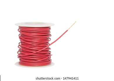 Copper wire spool. Red insulated wire wound up on plastic spindle. End of wire is stripped showing bare copper. Isolated on a white background. Room for text, copy space. Horizontal photo.