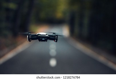Copter flies in the forest. On the street autumn twilight.